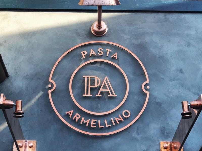 brushed flat cut copper metal logo outside restaurant