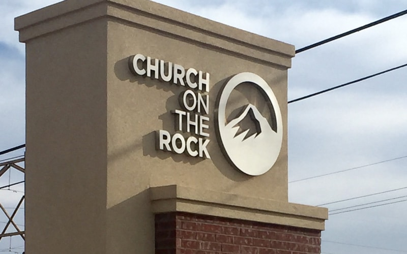 Fabricated brushed stainless steel letters and logo for church mounted on stucco monument