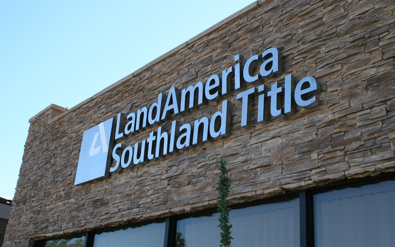 Brushed Cast Aluminum Letters with white vinyl logo mounted on stacked stone building outside