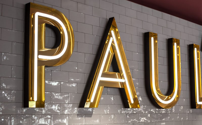 Open Faced Illuminated Letters with LED Neon in polished shiny gold mounted on subway tile restaurant wall