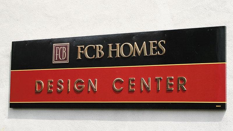 polished bronze metal letters fcb homes outside