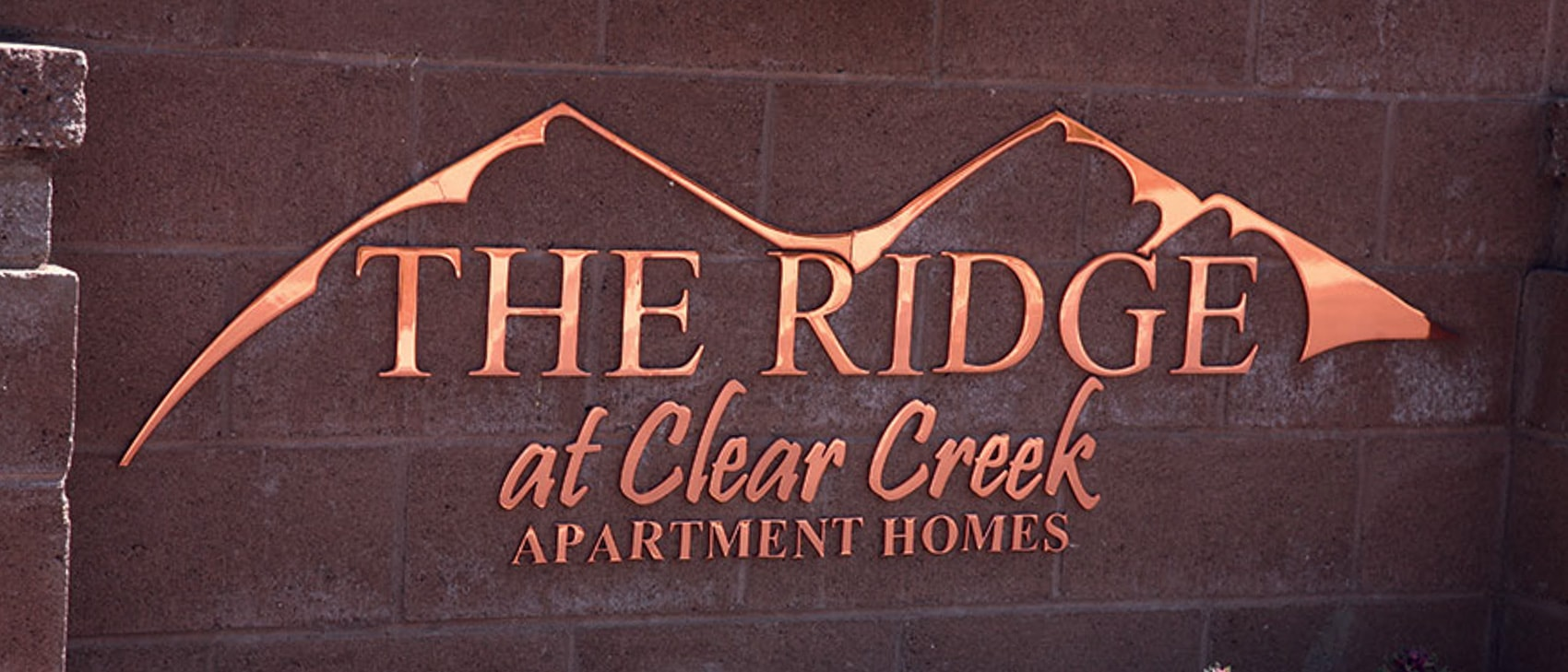 polished copper metal logo ridge apartment outside banner