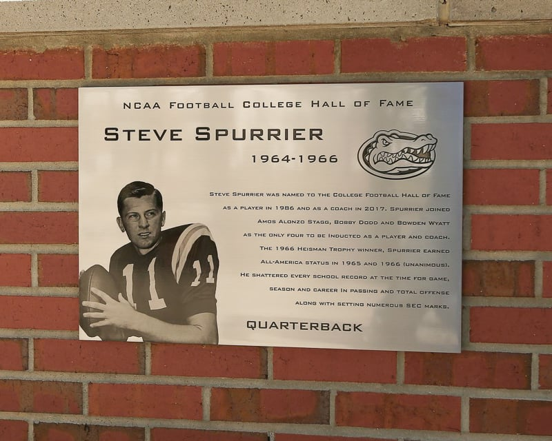 brushed etched stainless steel plaque with etched image portrait mounted outside on brick university stadium