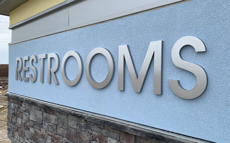 thick brushed aluminum letters mounted outside on restroom building