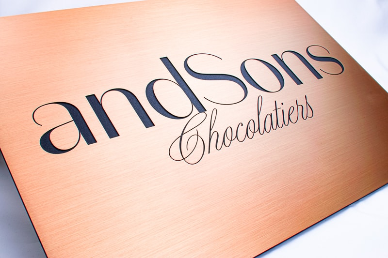 brushed etched copper plaque with black cursive writing for chocolate store