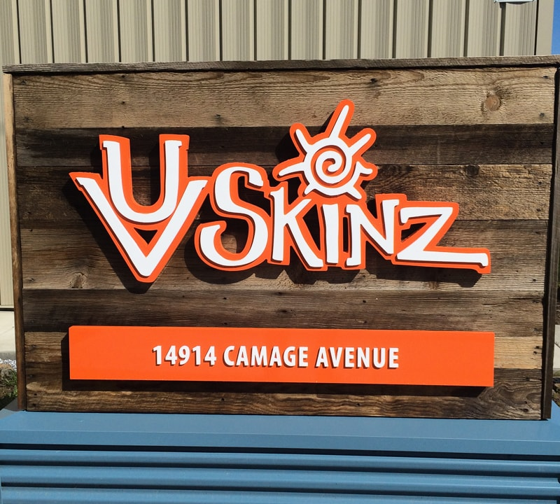 layered acrylic logo sign in orange and white mounted outside on wood planks