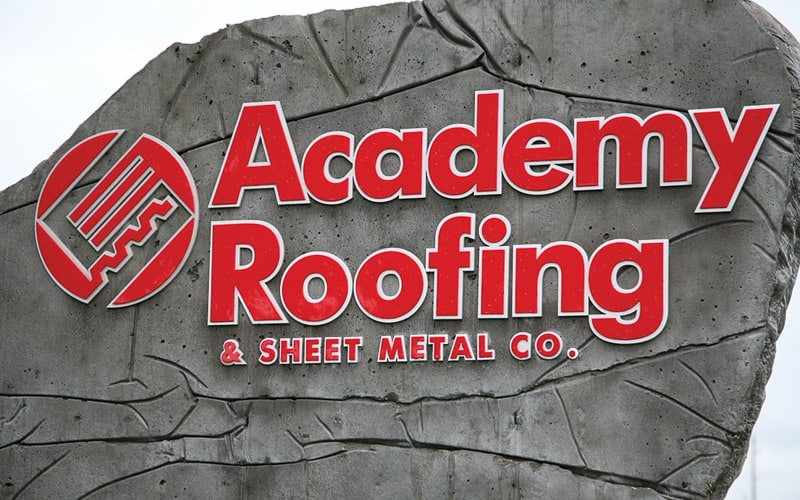 layered red and white acrylic letters and logo mounted outside on boulder for business