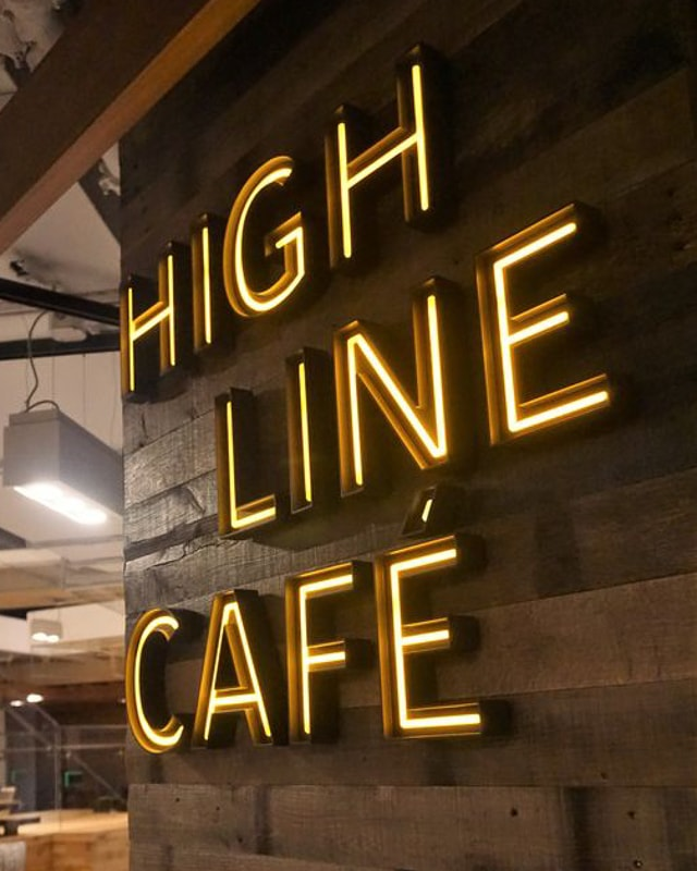 led acrylic faux neon yellow warm white led on painted black letters mounted inside coffe shop wood plank wall