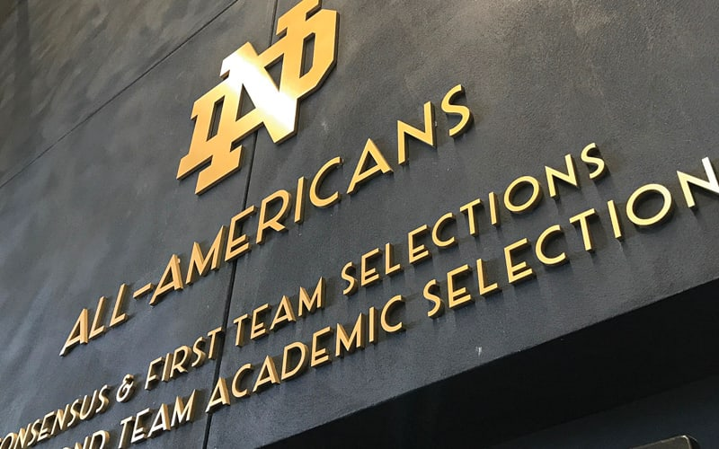metal faced acrylic letters brushed brass on gold acrylic mounted flush notre dame university athletics