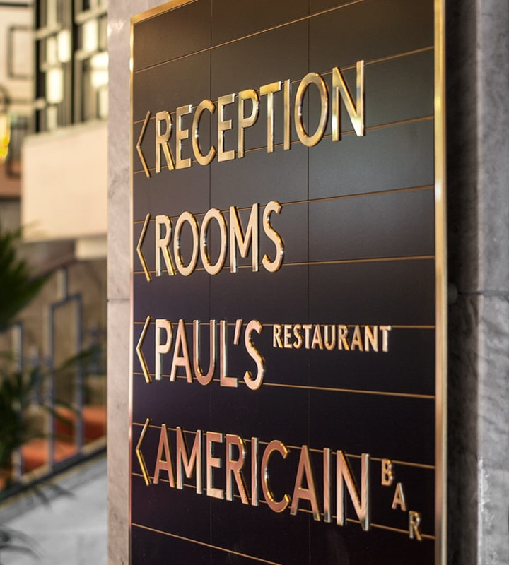 polished brass plaque wayfinding directional sign for hotel lobby