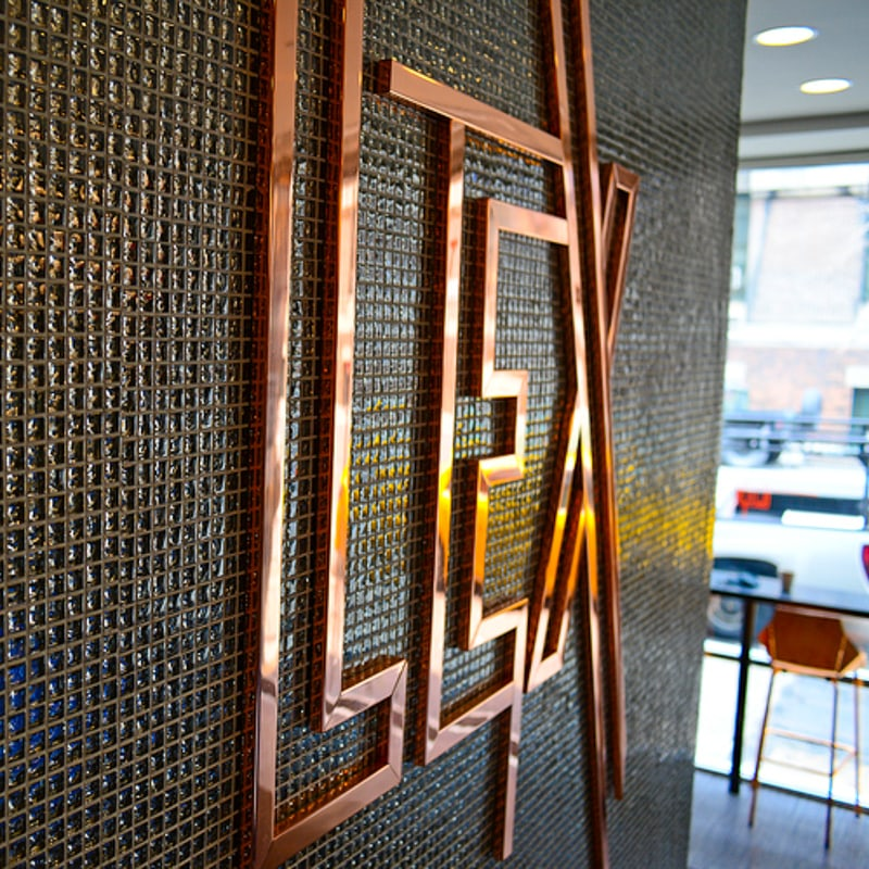 mirror polished copper metal letters inside hotel lobby