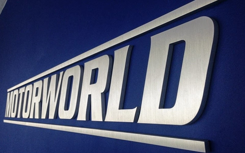 "1/2"" thick brushed aluminum letters and logo for motor world lobby mounted on blue office wall"