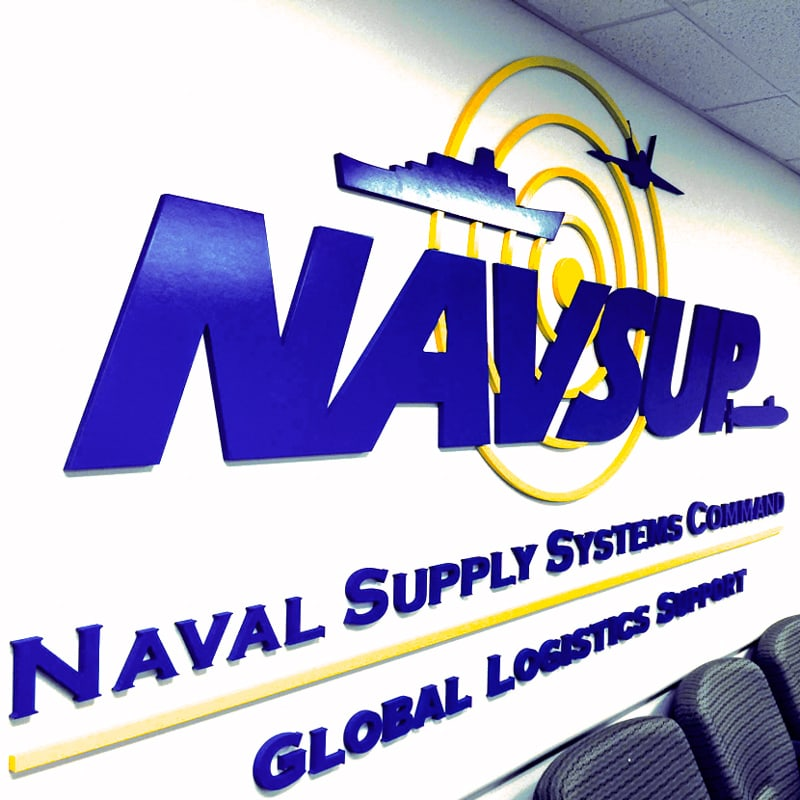 painted foam logo in blue and yellow mounted on navy military lobby wall
