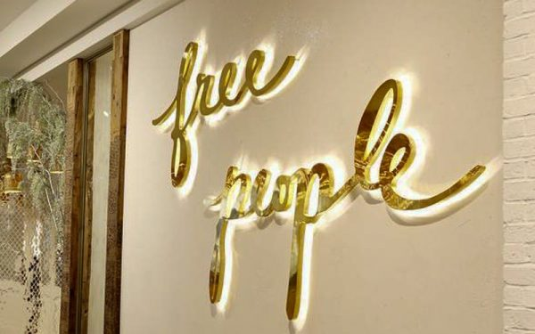 backlit mirror polished gold brass letters with LED halo lit free people sign
