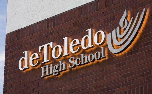 backlit halolit stainless steel letters and logo with warm LEDs outside school on brick