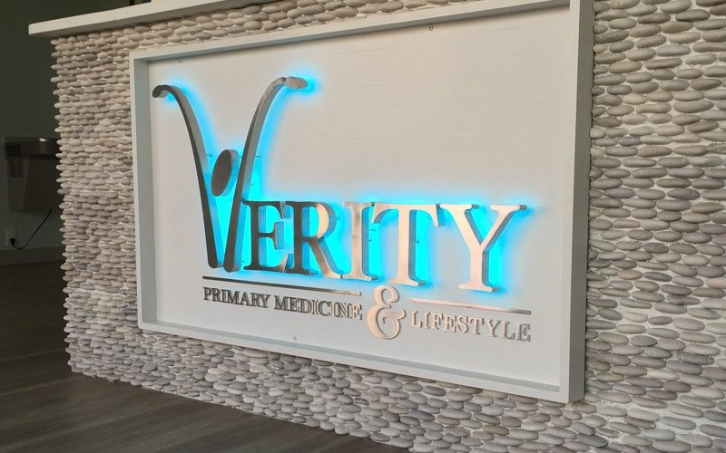 backlit halo letters with RGB blue LEDs in brushed stainless steel mounted inside medical lobby
