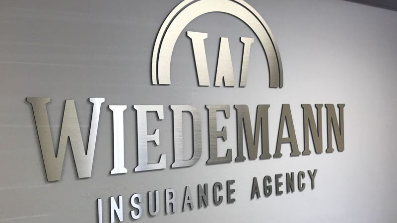 metal faced acrylic sign in brushed aluminum on black acrylic mounted for Widemann Insurance interior lobby wall