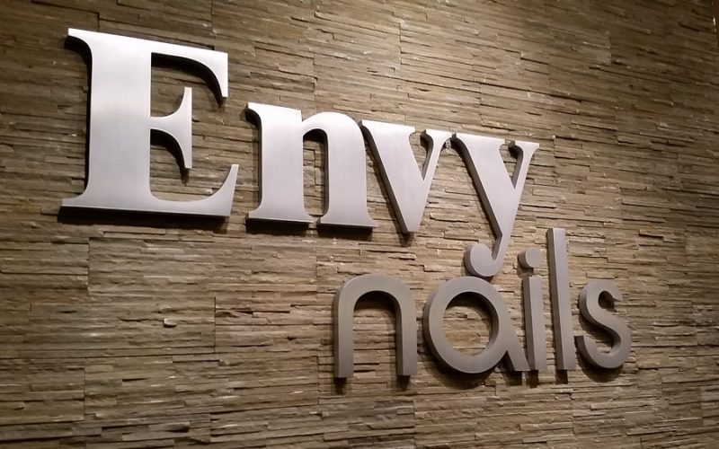 thick brushed cast aluminum letters for nail salon mounted inside lobby on stone wall