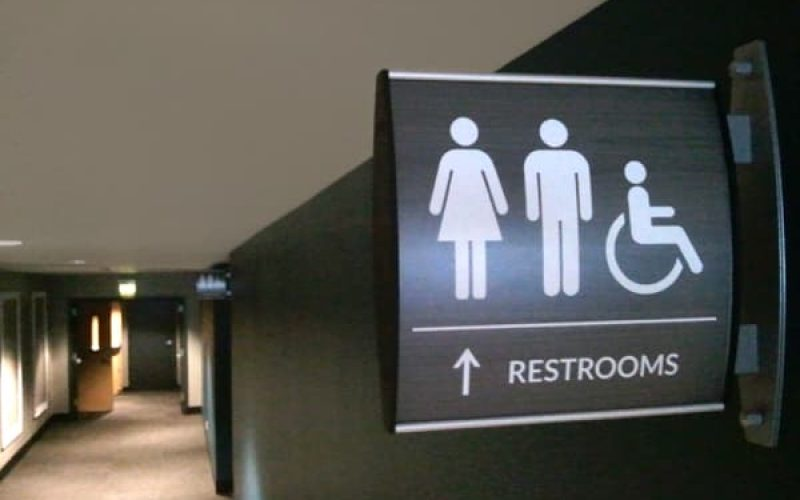 projected curved wall sign with removable face for restroom