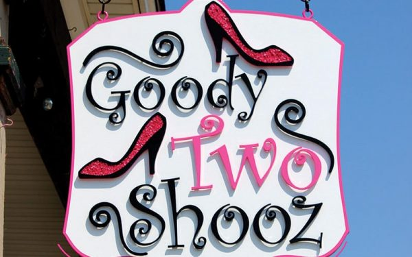 painted black and pink acrylic letters for retail store on hanging panel blade sign