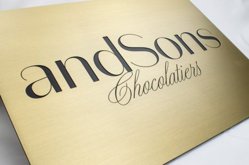 brushed etched brass plaque with black cursive writing for chocolate store
