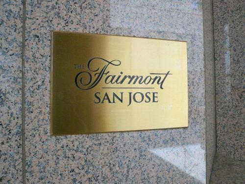 brushed etched brass plaque with black text and logo for outside hotel
