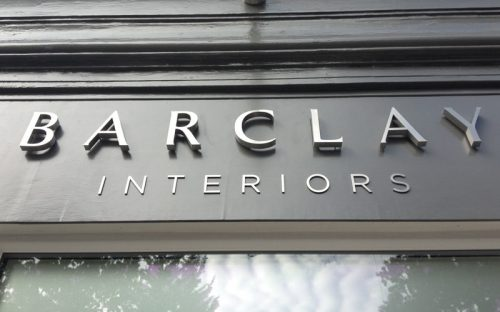 thick fabricated brushed stainless steel letters mounted outside storefront