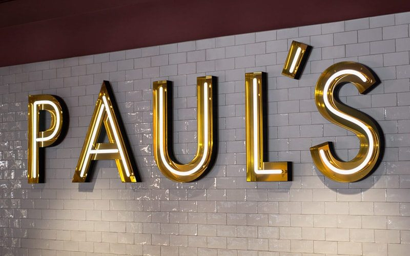 open faced LED neon channel letters in shiny polished gold mounted on subway tile for restaurant