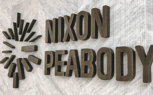 dark oxidized oil rubbed brass letters and logo mounted on tiled lobby wall nixon peabody law
