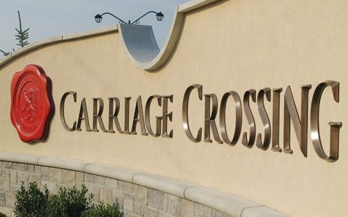 brushed oxidized oil rubbed bronze letters mounted on stucco monument for neighborhood entrance