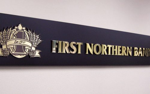 polished mirror brass letters mounted on black panel inside bank lobby
