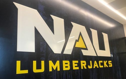 custom acrylic letters and logo in white and yellow glossy for inside university athletics facility